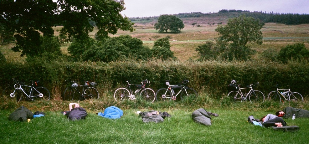Six people sleeping in bivvy bags in a field. There are bikes propped against a hedge in the backgroud.